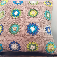 Crochet Cushion in a vibrant mix of blues, greens and creams.