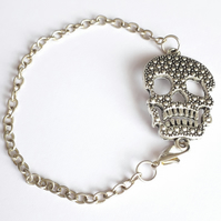 Silver coloured filigree skull charm link bracelet