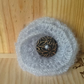 Pale grey knitted flower brooch.