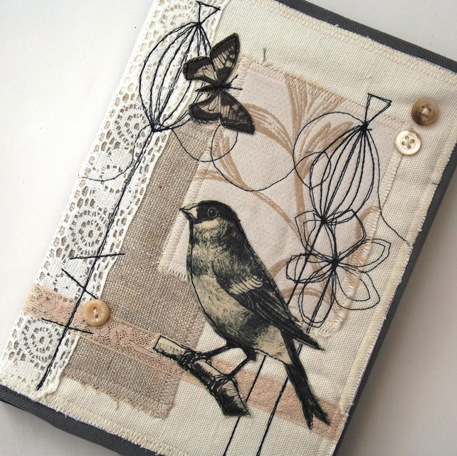 Collaged and embroidered covered notebook.