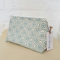 Zipped cosmetic bag in a teal geometric fabric