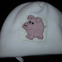 Baby hat with pig applique on white fleece