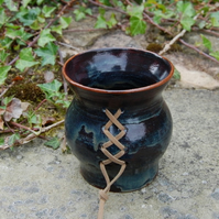 Handthrown ceramic 'corset' pot with leather detail.