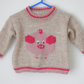 Hand knitted children's picture jumper with a pig design