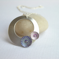 Silver coloured aluminium circle pendant with pink and purple discs
