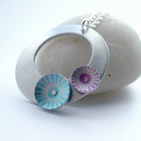 Silver coloured aluminium circle pendant with pink and blue discs