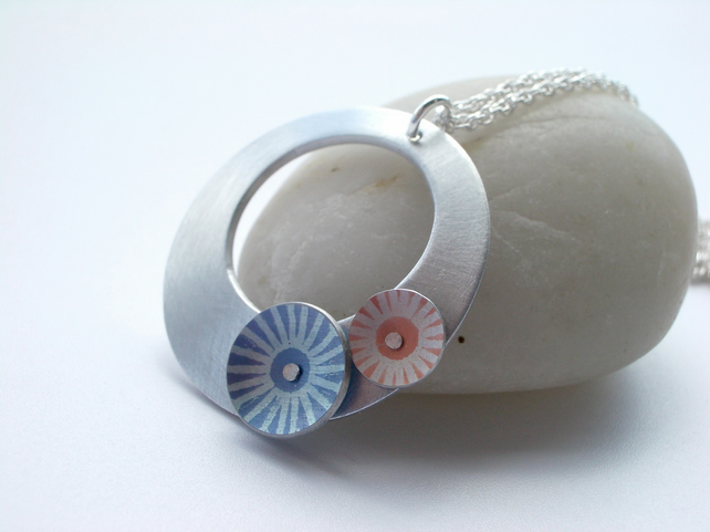 Silver coloured aluminium disc pendant necklace with blue and orange circles