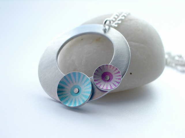 Silver coloured aluminium circle pendant with pink and blue circles
