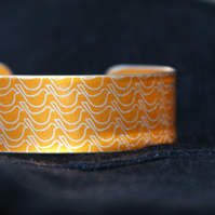Orange bird print aluminium cuff