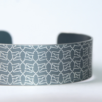 Grey aluminium cuff with bee pattern
