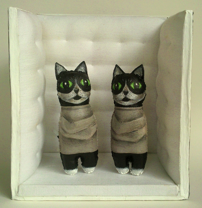 Cats in straitjackets in a functioning padded cell. Small sculpture.