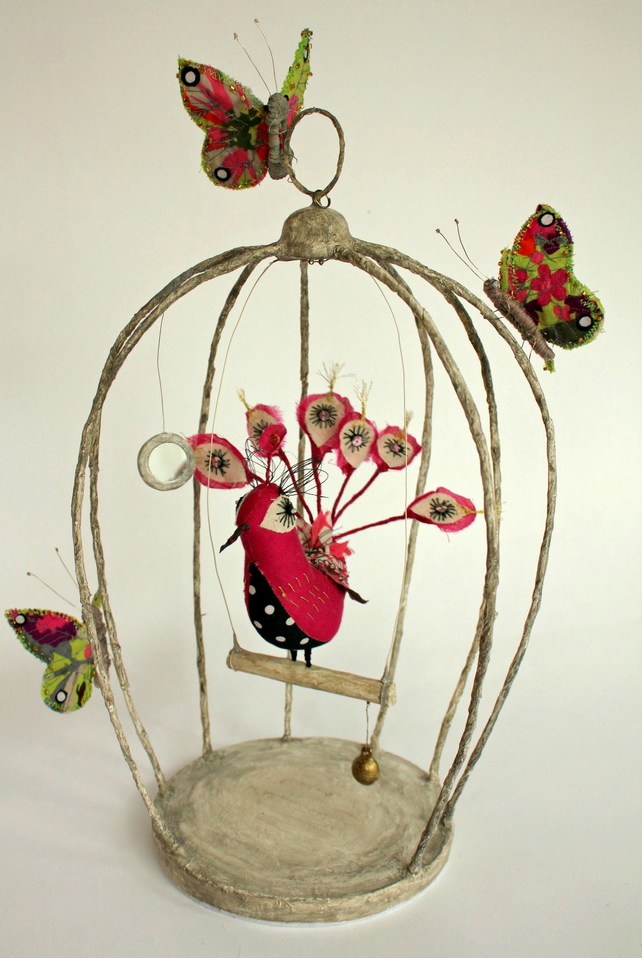 Birdcage with peacock and butterflies, mirror and bell.