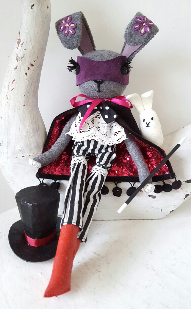 Grey rabbit doll, magician with white rabbit in top hat and magic wand.