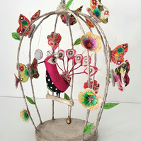 Textile peacock in a birdcage, adorned with embroidered butterflies and flowers.