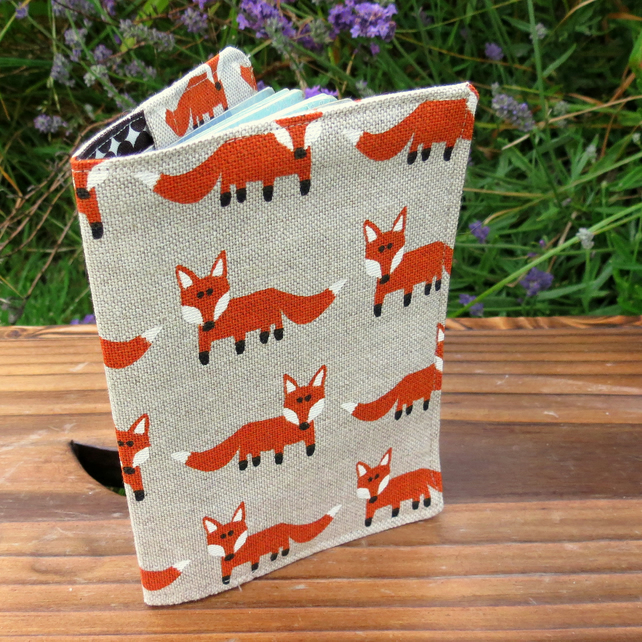 A fabric passport cover with a whimsical fox design.