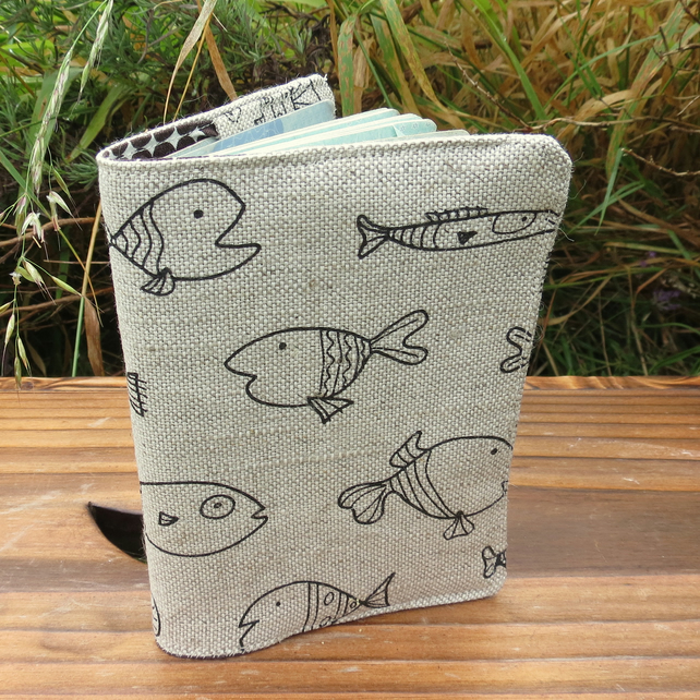 A fabric passport cover with a whimsical fish design.