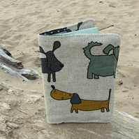 A linen passport sleeve with a whimsical dogs design.