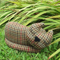 A snoozy cat doorstop made from tactile pure wool.