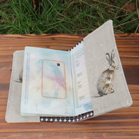 A fabric passport cover with a whimsical hare design.