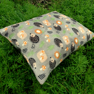 A pet cushion with a whimsical hedgehogs design.  Dog bed.  Cat bed.