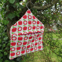 A peg bag with a red apples design.