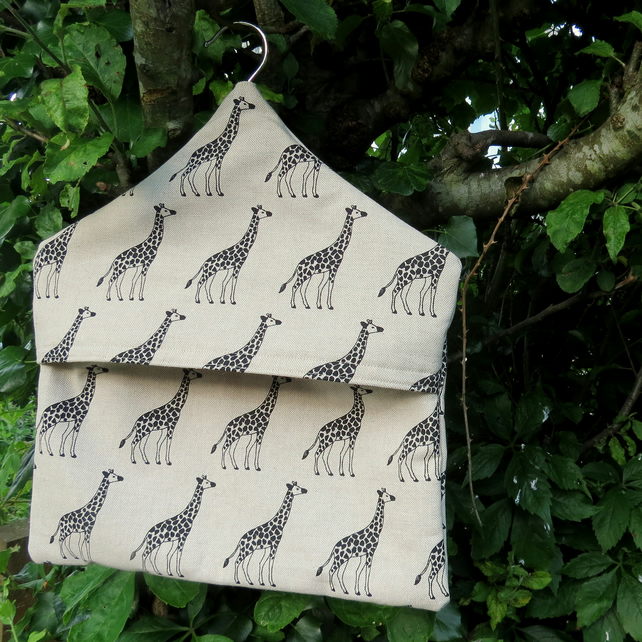 A peg bag with a giraffes design.  Peg storage.