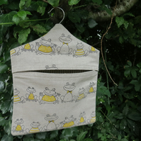 A peg bag with a quirky frogs design.  Peg storage.