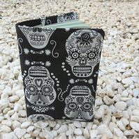 A passport sleeve with a skulls design.  Passport cover.  Halloween.