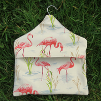 A peg bag with a pink flamingos design.  Laundry.  Peg storage.