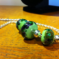 Grasshopper green lampwork glass beads with green, purple and brown spots