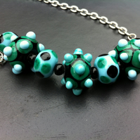 spotty and bumpy lampwork glass earrings and necklace in blue green and black