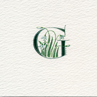 Initial letter G' handpainted in dark green with snowdrops
