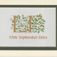 Two Wedding initials in gold with white roses and green leaves