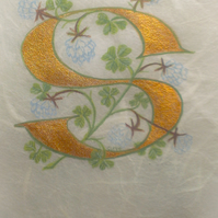 Initial letter S in gold with white clover on silk fibre paper