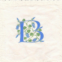 Initial letter 'B' in turquoise with bluebells on silk fibre paper.