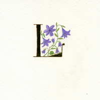Initial letter L in 24c gold leaf with purple lilies and harebells