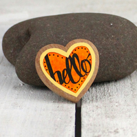 Hand drawn wooden HELLO brooch in black on orange