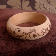 Hand pyrographed wooden bangles with a flowery scroll design or barbed wire .