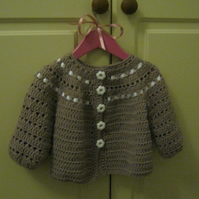 Crochet beige jacket for little girls with white ribbon and buttons
