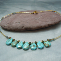 An Egyptian inspired necklace with teardrop Turquoise beads & gold plate beads