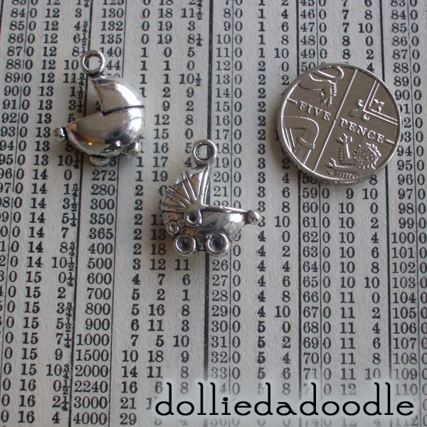 4 silver coloured baby carriage charms
