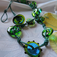 Handmade blue and green lampwork beads with knotted teal leather cord