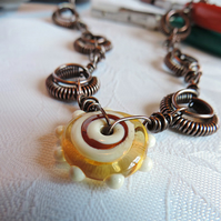 Amber and cream glass bead pendant with hand forged copper links