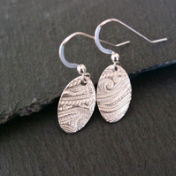Oval silver earrings with a beach wave pattern pure silver clay sterling silver