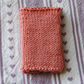 Hand knitted needle case and contents - coral pink