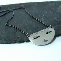 Half round pendant, silver face with green eyes.