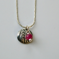 Little patterned disc and ruby pendant