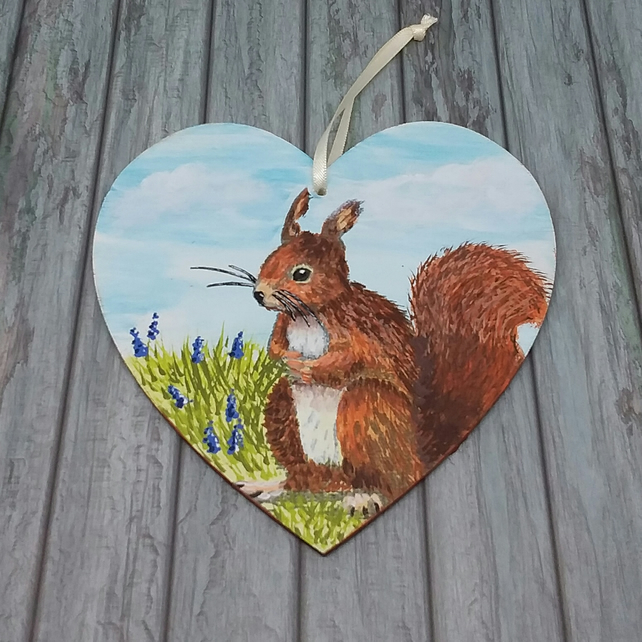 Red squirrel hanging heart