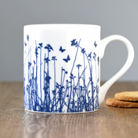 Fine bone china blue butterflies silhouetted over meadow mug