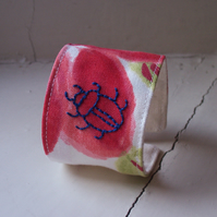 Hand embroidered textile cuff with beetle on poppy fabric